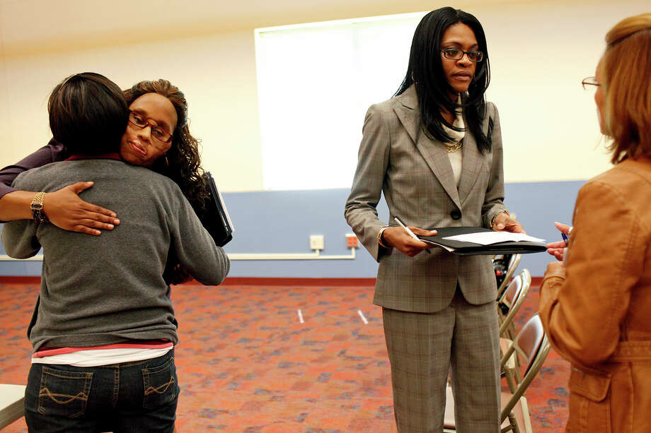 Carolyn Thomas (left, facing camera) of Waco embraces student Madalitt Martinez, while fellow domestic violence survivor Dee Anna Morgan-Alexander of Fort Worth, who was shot in the face by her spouse, talks with student Maria Del Valle (far right) at Palo Alto College. The event was held to mark National Domestic Violence Awareness Day. Photo: Lisa Krantz/lkrantz@express-news.net / SAN ANTONIO EXPRESS-NEWS
