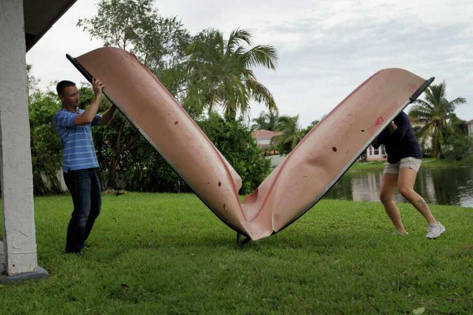Jason Grodensky (L) and Maria Rosario prepare to carry her canoe to a trash pile after it was bent in half by after a tornado hit her home on October 19, 2011 in Sunrise, Florida. The tornado hit last night and caused damage to homes in the area but there were no reports of fatalities. Photo: Joe Raedle, Getty / 2011 Getty Images