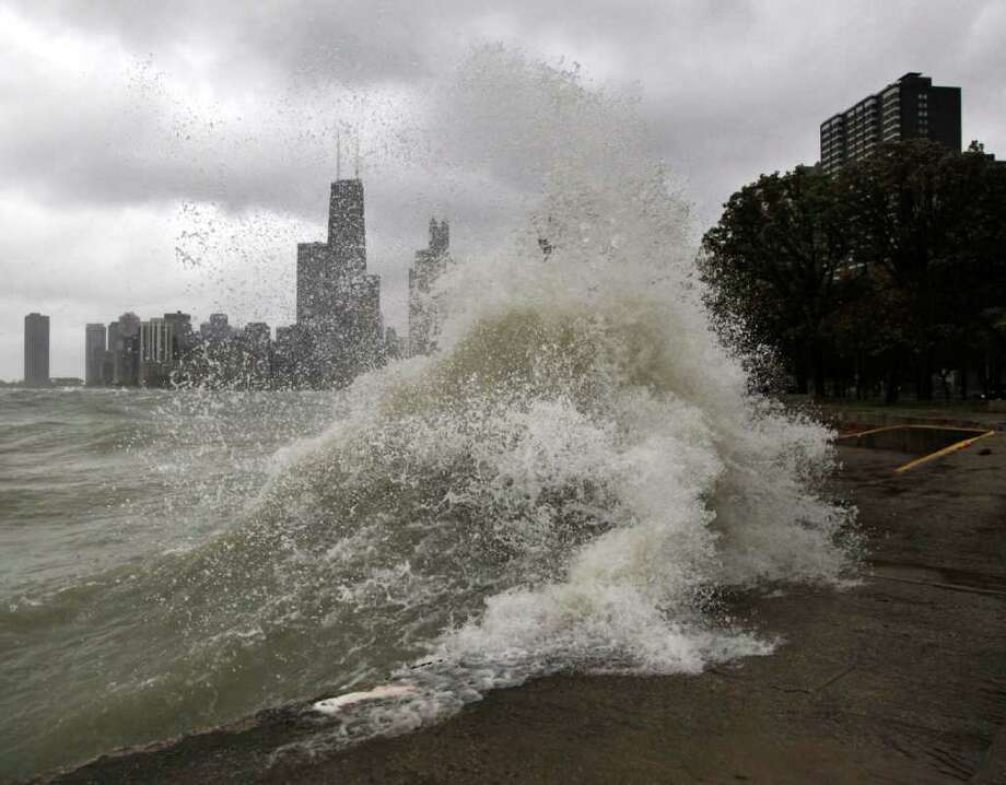 Waves crash along the Lake Michigan bike path wall at Chicago's North Ave. beach Wednesday, Oct. 19, 2011. The Office of Emergency Management issued a public safety reminder Wednesday, saying that the bike path is closed because of expected wind gusts of up to 50 mph, waves of up to 25 feet and heavy rains. Photo: Charles Rex Arbogast, Associated Press / AP