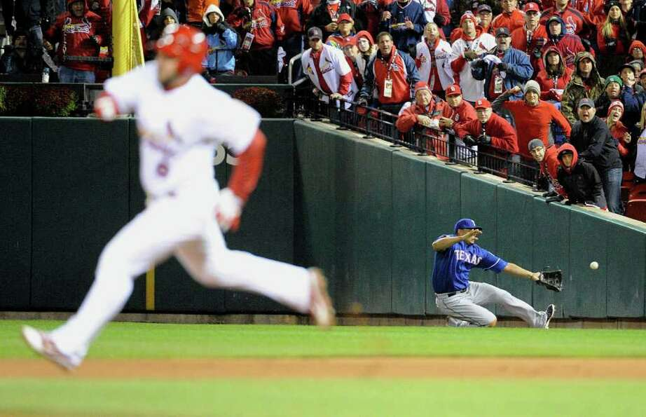 St. Louis Cardinals' Nick Punto heads for home as Texas Rangers right fielder Nelson Cruz can't hand