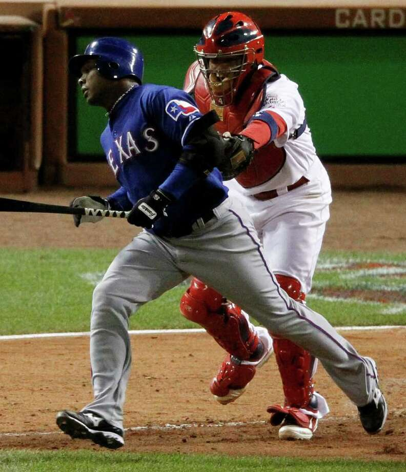 St. Louis Cardinals catcher Yadier Molina tags out Texas Rangers' Esteban German after German struck out swinging and the ball was dropped during the seventh inning of Game 1 of baseball's World Series Wednesday, Oct. 19, 2011, in St. Louis. (AP Photo/Jeff Roberson) Photo: Jeff Roberson, Associated Press / AP
