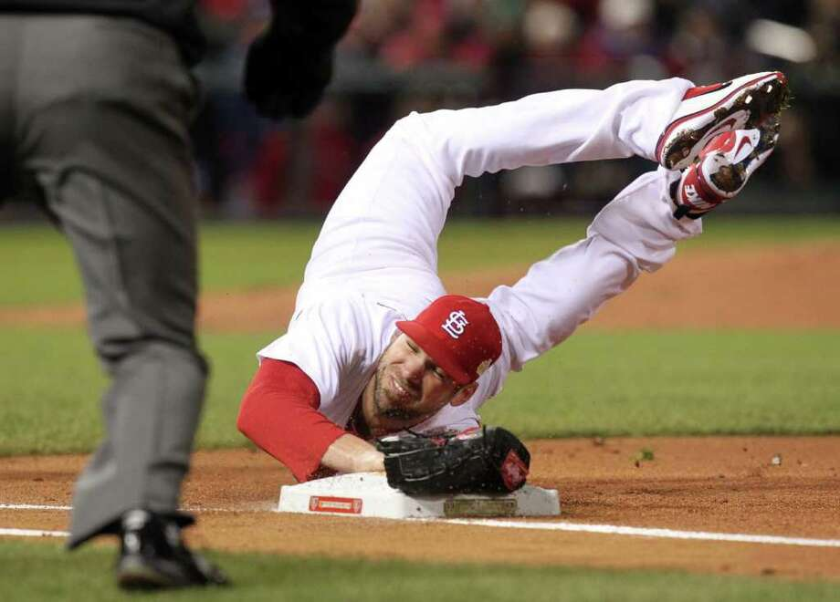 St. Louis Cardinals starting pitcher Chris Carpenter dives to first base for a first-inning out against the Texas Rangers in Game 1 of the World Series at Busch Stadium in St. Louis, Missouri, on Wednesday, October 19, 2011. Photo: Michael Ainsworth, McClatchy-Tribune News Service / Dallas Morning News