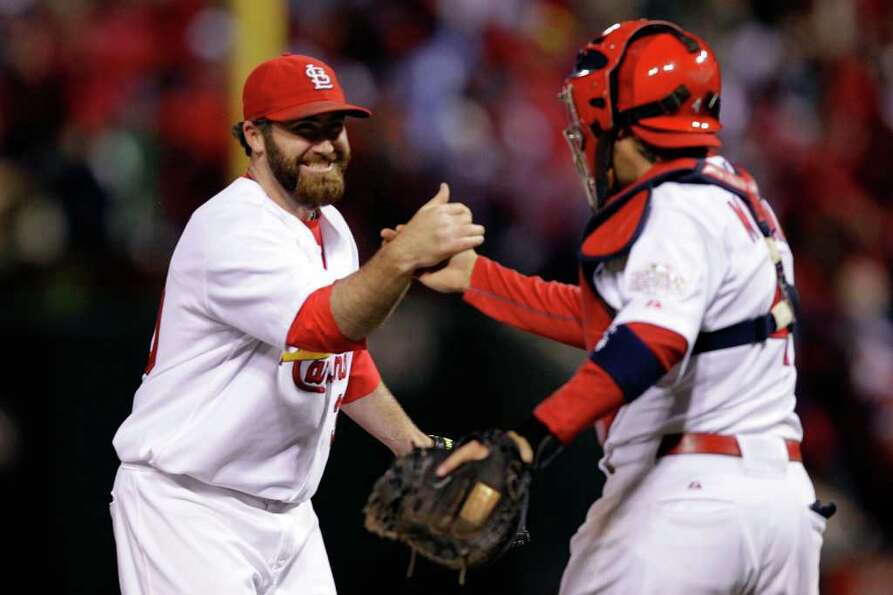 Jason Motte #30 and Yadier Molina #4 of the St. Louis Cardinals celebrate after defeating the Texas