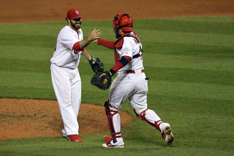Jason Motte #30 and Yadier Molina #4 of the St. Louis Cardinals celebrate after defeating the Texas Rangers 3-2 during Game One of the MLB World Series at Busch Stadium on October 19, 2011 in St Louis, Missouri. Photo: Ezra Shaw, Getty / 2011 Getty Images