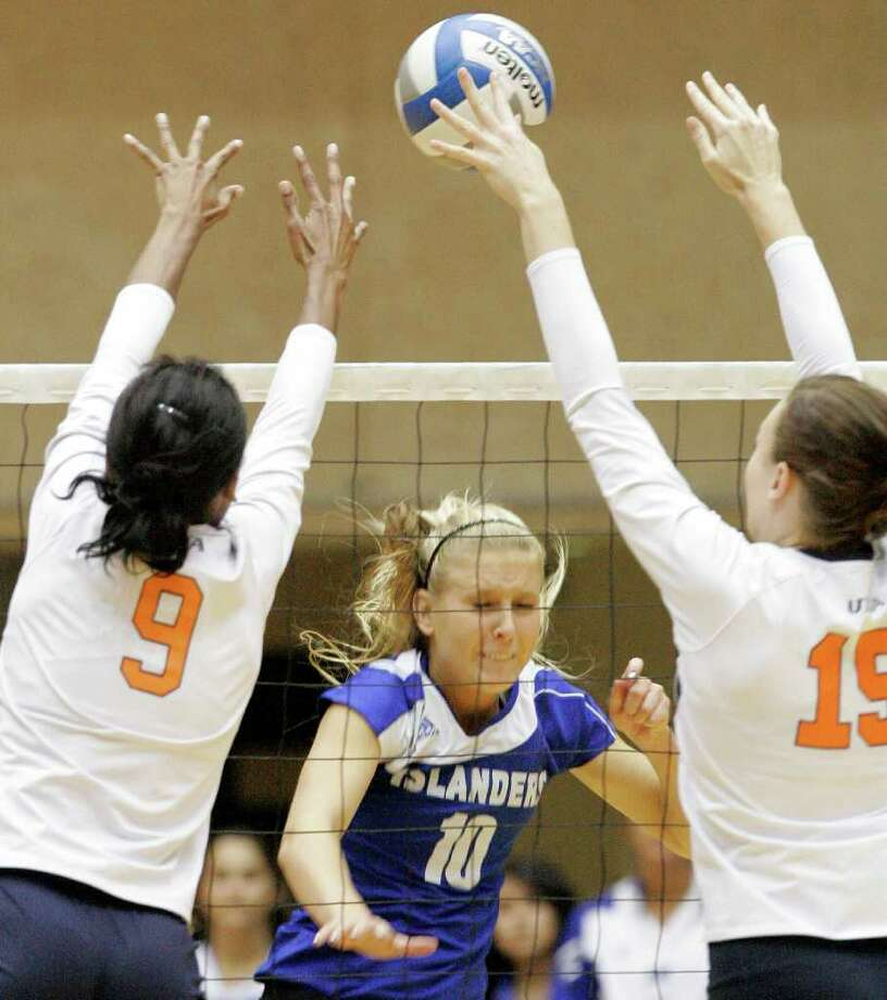 UTSA's Brittney Malloy, left, and Whitney Walls, right, defend against Texas A&M-Corpus Christi's Brianna Brink during a Southland Conference college volleyball game, Wednesday, Oct. 19, 2011, at UTSA. Photo: Darren Abate, Darren Abate/Special To The Express-News