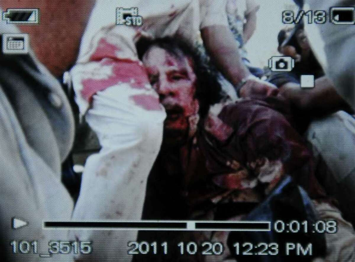 An image captured off a cellular phone camera shows the arrest of Libya's strongman Moamer Kadhafi in Sirte on October 20, 2011. A Libyan National Transitional Council (NTC) commander had told AFP that Kadhafi was captured as his hometown Sirte was falling, adding that the ousted strongman was badly wounded. AFP PHOTO/PHILIPPE DESMAZES