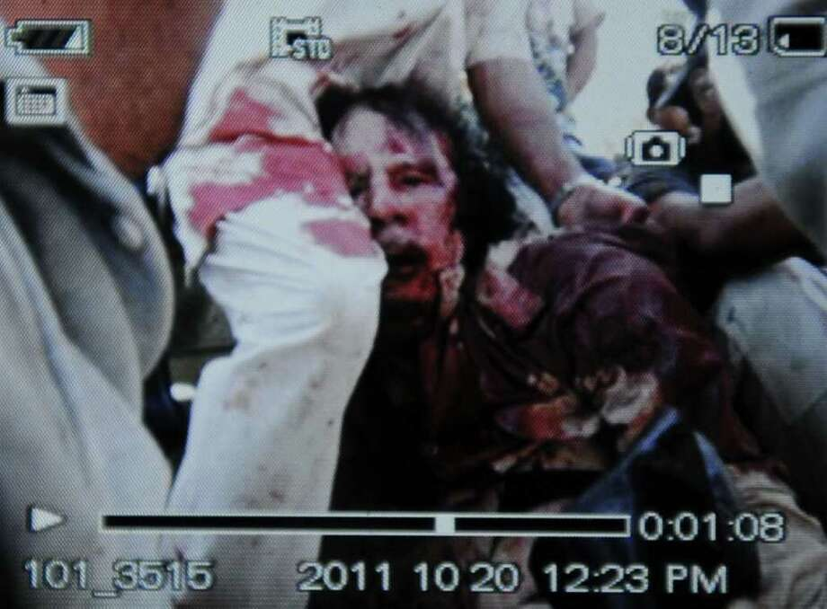 An image captured off a cellular phone camera shows the arrest of Libya's strongman Moamer Kadhafi in Sirte on October 20, 2011.  A Libyan National Transitional Council (NTC) commander had told AFP that Kadhafi was captured as his hometown Sirte was falling, adding that the ousted strongman was badly wounded.     AFP PHOTO/PHILIPPE DESMAZES Photo: PHILIPPE DESMAZES, AFP/Getty Images / AFP