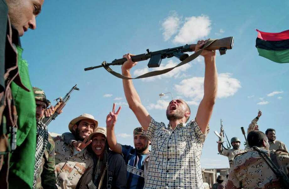 Revolutionary fighters celebrate the capture of Sirte, Libya, Thursday, Oct. 20, 2011. Officials in Libya's transitional government said Moammar Gadhafi was captured and possibly killed Thursday when revolutionary forces overwhelmed his hometown, Sirte, the last major bastion of resistance two months after the regime fell. (AP Photo/David Sperry) Photo: David Sperry, ASSOCIATED PRESS / AP2011