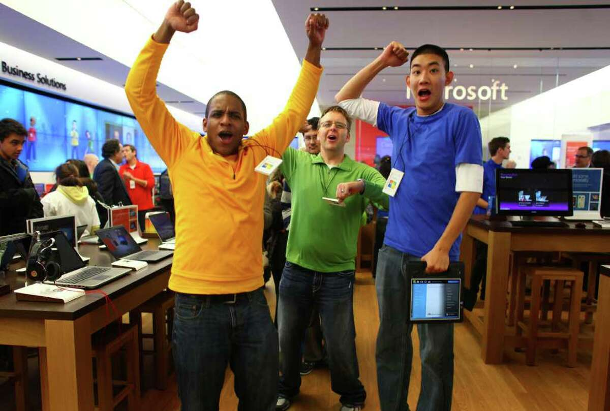 Microsoft Store employees cheer as customers begin to stream into the new retail store during its grand opening at University Village on Thursday, October 20, 2011.