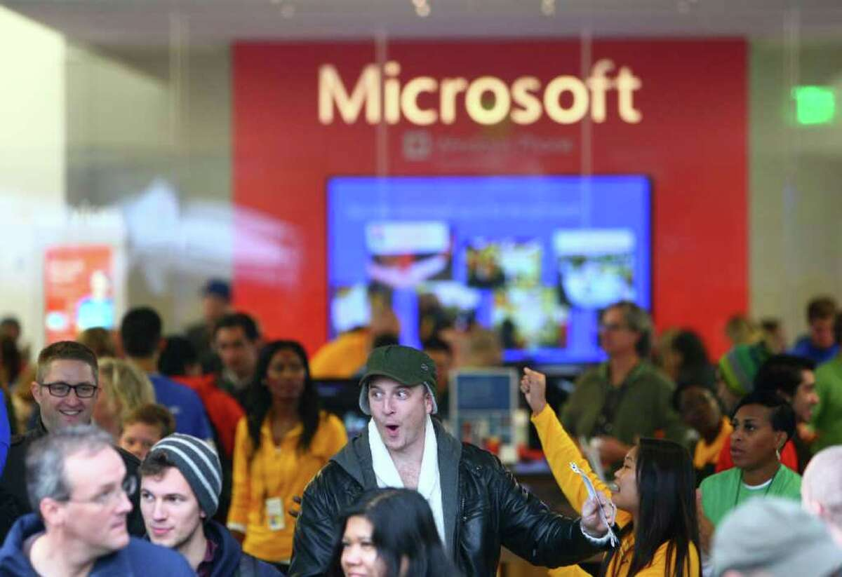 People leave the new Microsoft Store after they secured passes to concerts by The Black Keys and OneRepublic during the opening celebration of the new retail store at University Village on Thursday, October 20, 2011.