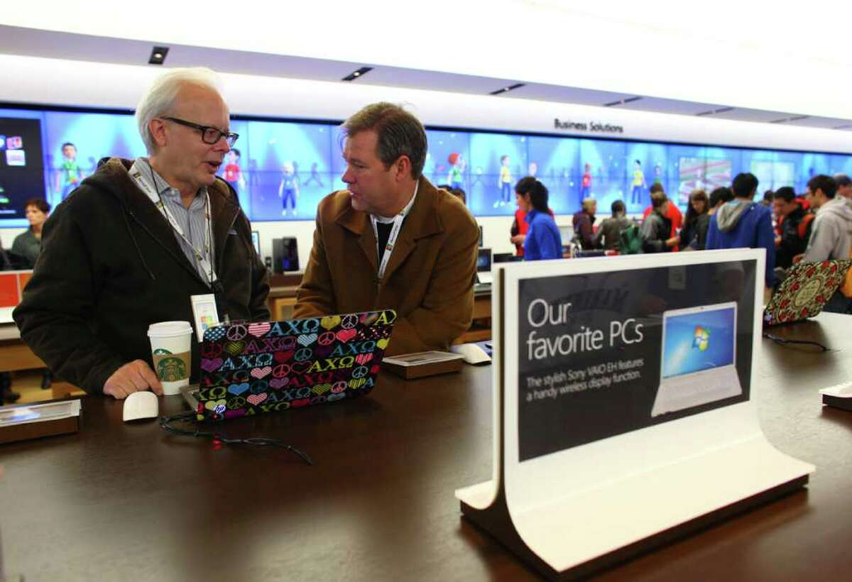 Former Microsoft Chief Technical Officer and Chief Software Architect Ray Ozzie, left, speaks with corporate vice president of Retail Stores David Porter during the opening of the new Microsoft retail store at University Village on Thursday, October 20, 2011.