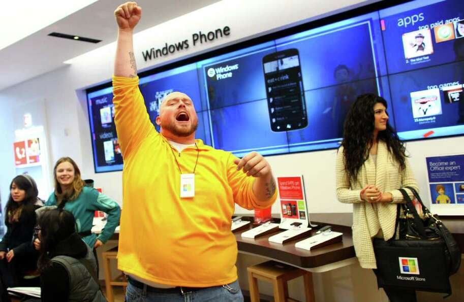 A Microsoft Store employee cheers as customers begin to stream into the new retail store during its