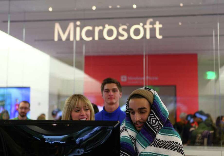 Microsoft Store employee Jennifer Hollingsworth speaks with David Escobedo at a computer as customers begin to stream into the new retail store during its grand opening at University Village on Thursday, October 20, 2011. Photo: JOSHUA TRUJILLO / SEATTLEPI.COM