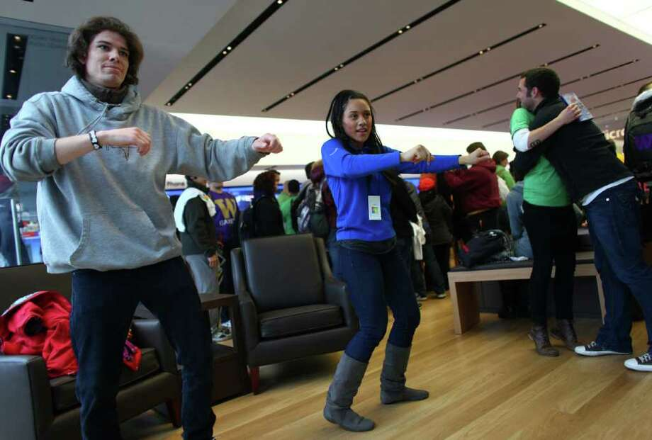 Michael Moorman, left and Microsoft Store employee Lajiah Kirby-Hairston play an Xbox game as customers begin to stream into the new retail store during its grand opening at University Village on Thursday, October 20, 2011. Photo: JOSHUA TRUJILLO / SEATTLEPI.COM