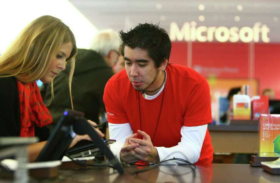Microsoft Store employee Michael Simons helps Esther Haak with a Samsung tablet at the new retail store during its grand opening at University Village on Thursday, October 20, 2011. Photo: JOSHUA TRUJILLO / SEATTLEPI.COM