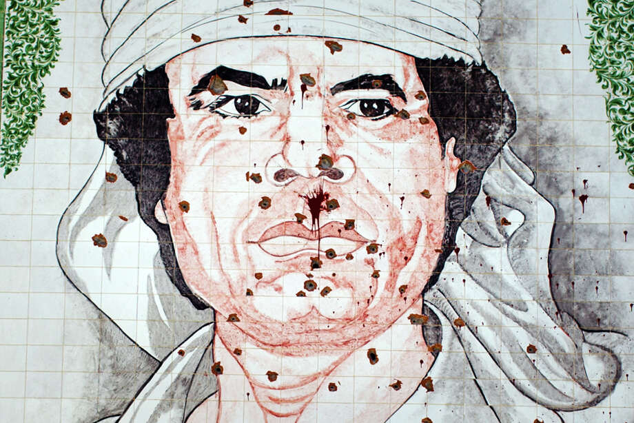 TRIPOLI, LIBYA - AUGUST 29: A mosaic of Gaddafi is seen on the wall of a building, riddled with bullett holes, on August 29, 2011 in Tripoli, Libya. Whilst the rebels to seem to be in control of the capital, life is difficult for most. The majority of the city is without running water and electricity. (Photo by Daniel Berehulak/Getty Images) Photo: Daniel Berehulak, Getty Images / 2011 Getty Images