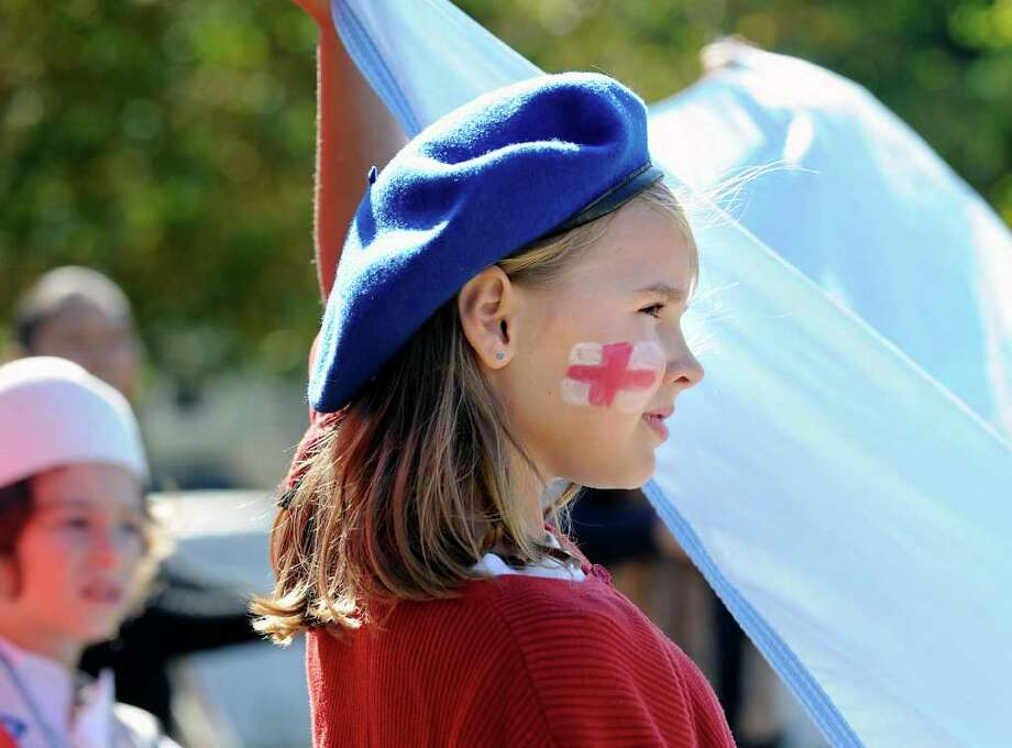 Wearing the Cross of St. George on her face to represent Great Britain, Isabella Meath, 10, a fifth grader at Julian Curtiss School carries the United Nations flag during the United Nations Day celebration at the school, in Greenwich, Thursday, Oct. 20, 2011. Photo: Bob Luckey / Greenwich Time