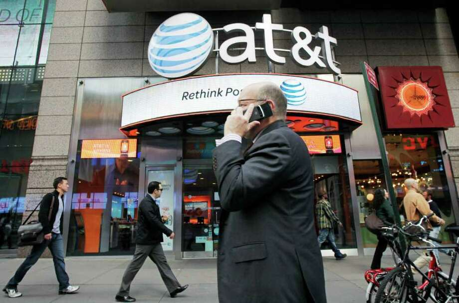 In this Oct. 18, 2011 photo, a man using a cell phone passes an AT&T store, in New York.   AT&T Inc. on Thursday, Oct. 20, 2011,  reported a decline in the number of iPhones activated in its latest quarter, as buyers waited for the new model. ((AP Photo/Mark Lennihan) Photo: Mark Lennihan / AP