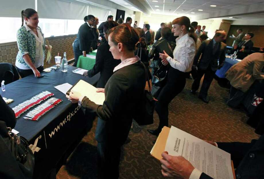 Job seekers crowd around tables to get information and drop off resumes during a job fair in Boston Monday, Oct. 17, 2011. Fewer people likely applied for unemployment benefits last week, suggesting the job market may be improving slightly. (AP Photo/Elise Amendola) Photo: Elise Amendola / AP