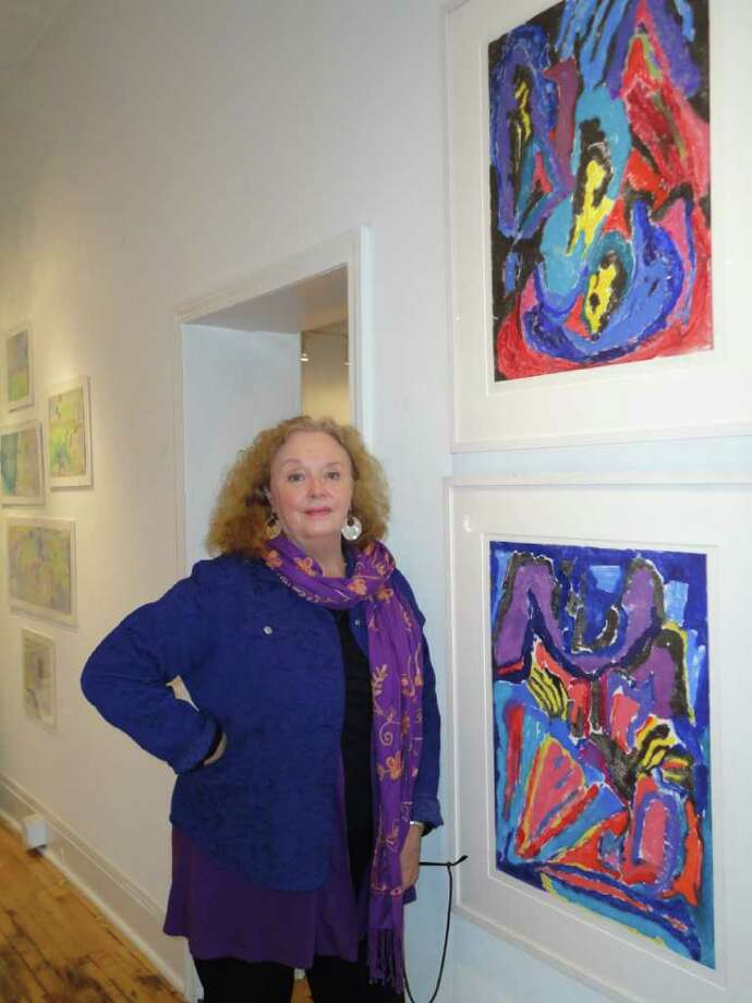 "Mary Louise Long, a member artist of ArtPlace gallery in downtown Fairfield, stands by two of her paintings  in ""The Last Picture Show"" exhibit, the final one in the Unquowa Road space. Photo: Meg Barone / Fairfield Citizen freelance"