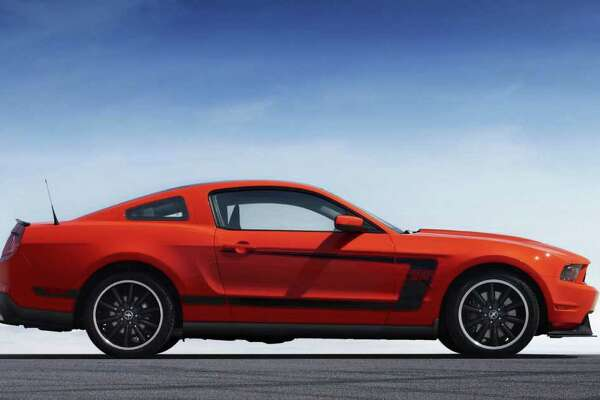 """The Boss 302 has special wheels and an exterior paint scheme that includes either a black or white top and matching side """"C"""" stripes. COURTESY OF FORD MOTOR CO."""