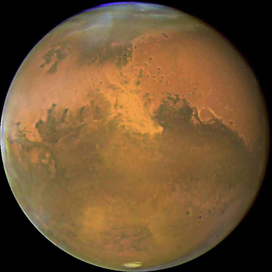 This NASA Hubble Space Telescope image released 03 November, 2005 shows Mars 28 October, within a day of its closest approach to Earth on the night of 29 October. The large regional dust storm(C) appears as the brighter, redder cloudy region in the middle of the planet's disk. This storm, which measures 930 miles (1500 km) has been churning in the planet's equatorial regions for several weeks now, and it is likely responsible for the reddish, dusty haze and other dust clouds seen across this hemisphere of the planet. Hubble's Advanced Camera for Surveys High Resolution Imager took this image when the red planet was 43 million miles (69 million km) from Earth. Mars won't be this close again to Earth until 2018. Mars is now in its warmest months, closest to the Sun in its orbit, resulting in a smaller than normal south polar ice cap which has largely sublimated with the approaching summer.   AFP PHOTO/ NASA/ ESA  (Photo credit should read HO/AFP/Getty Images) Photo: HO / AFP