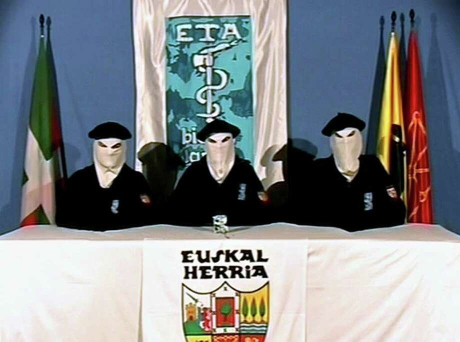FILE -  This video frame, seen in this March 22, 2006 file photo, which was released by the Basque separatist group ETA, shows three unidentified  people with their faces covered, wearing Basque berets and seated at a table in front of an ETA flag with a Basque Country symbol in foreground. The Basque daily Gara says the armed group ETA has issued a statement Thursday Oct. 20, 2011 saying it is ending its armed campaign and calls on Spain and France to open talks. (AP Photo/Basque Television, File) / BASQUE TELEVISION