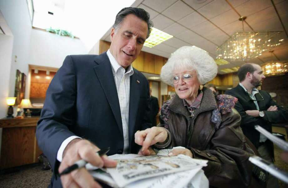 CHARLIE NEIBERGALL : ASSOCIATED PRESS  NAME ONLY: Republican presidential candidate Mitt Romney signs an autograph for Jeanne Dietrich, of Omaha, Neb., before speaking at an economic roundtable in Treynor, Iowa. Photo: Charlie Neibergall, ASSOCIATED PRESS / AP