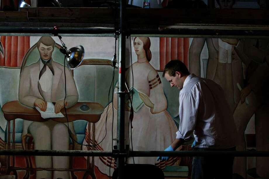 Nathan Sutton uses a cleaning solution to help restore the 76-year-old mural painted by Ruth Pershing Uhler in 1935 in the Julia Ideson Library, Thursday, Oct. 20, 2011. Photo: Johnny Hanson, Houston Chronicle / © 2011 Houston Chronicle