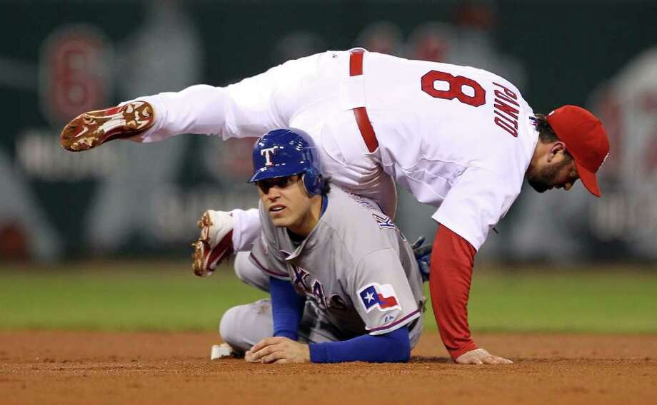 Nick Punto of the Cardinals turns the double play as Ian Kinsler of the Rangers slides into second base in the sixth inning. Photo: Ezra Shaw, Getty / 2011 Getty Images