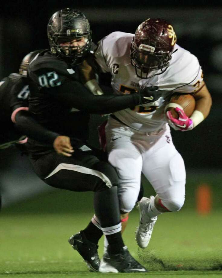 Deer Park's Clay De la Garza (right) tries to escape Pasadena Memorial's Mark McCneil's tackle during the first half of a high school football game, Thursday, October 20, 2011 at Veterans Memorial Stadium in Pasadena. Photo: Eric Christian Smith, For The Chronicle