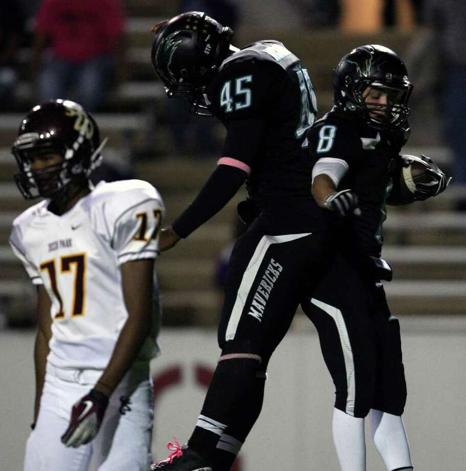 Pasadena Memorial's Chris Cargile (8) celebrates his 16-yard touchdown run with teammate Dorian Johnson as Deer Park's D.J. Lasua walks off the field. Photo: Eric Christian Smith, For The Chronicle