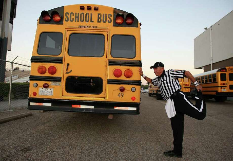 Umpire Dave Orton stretches by a school bus before officiating a high school football game between Pasadena Memorial and Deer Park. Photo: Eric Christian Smith, For The Chronicle