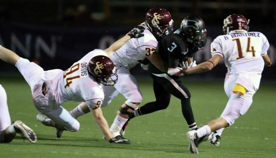 Pasadena Memorial's Reggie Turner (3) is tackled by Deer Park's Phillip Blake.