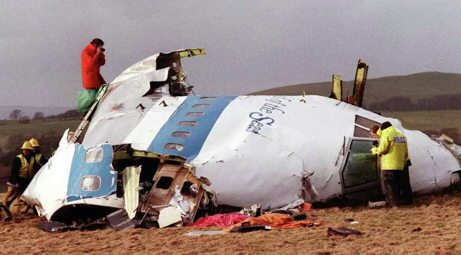 FILE - This  Dec. 22, 1988 file photo shows Police and investigators look at what remains of the flight deck of Pan Am 103 on a field in Lockerbie, Scotland. Moammar Gadhafi?s death on Oct. 20, 2011, resonates with the families who had loved ones on the airliner who held Gadhafi responsible for sanctioning the 1988 bombing that killed 270 people. (AP Photo/File) / AP1996