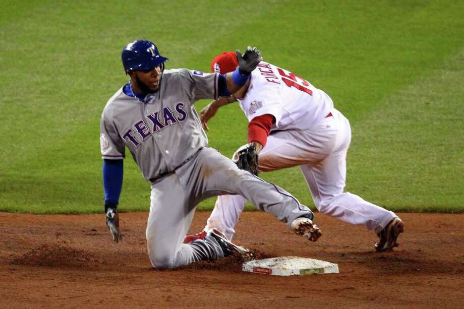 Elvis Andrus of the Rangers slides into second base ahead of the tag by Rafael Furcal. Photo: Dilip Vishwanat, Getty / 2011 Getty Images