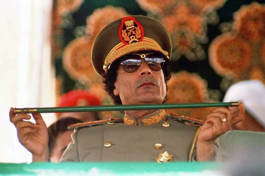 JOHN REDMAN : ASSOCIATED PRESS FILE xxxx: - In this Sept. 1, 1987 file photo, Libyan leader Col. Moammar Gadhafi, holds a baton as he sits to review Libyan troops during the 18th anniversary celebration of Libya's revolution in Tripoli.   A U.S. official says Libya's new government has told the United States that Gadhafi, 69,  is dead. The official said Libya's Transitional National Council informed U.S. officials in Libya of the development Thursday, Oct. 20, 2011.  His death on Thursday, confirmed by Prime Minister Mahmoud Jibril, came as Libyan fighters defeated Gadhafi's last holdouts in his hometown of Sirte, the last major site of resistance in the country. AP Photo/John Redman) Photo: John Redman / AP1987