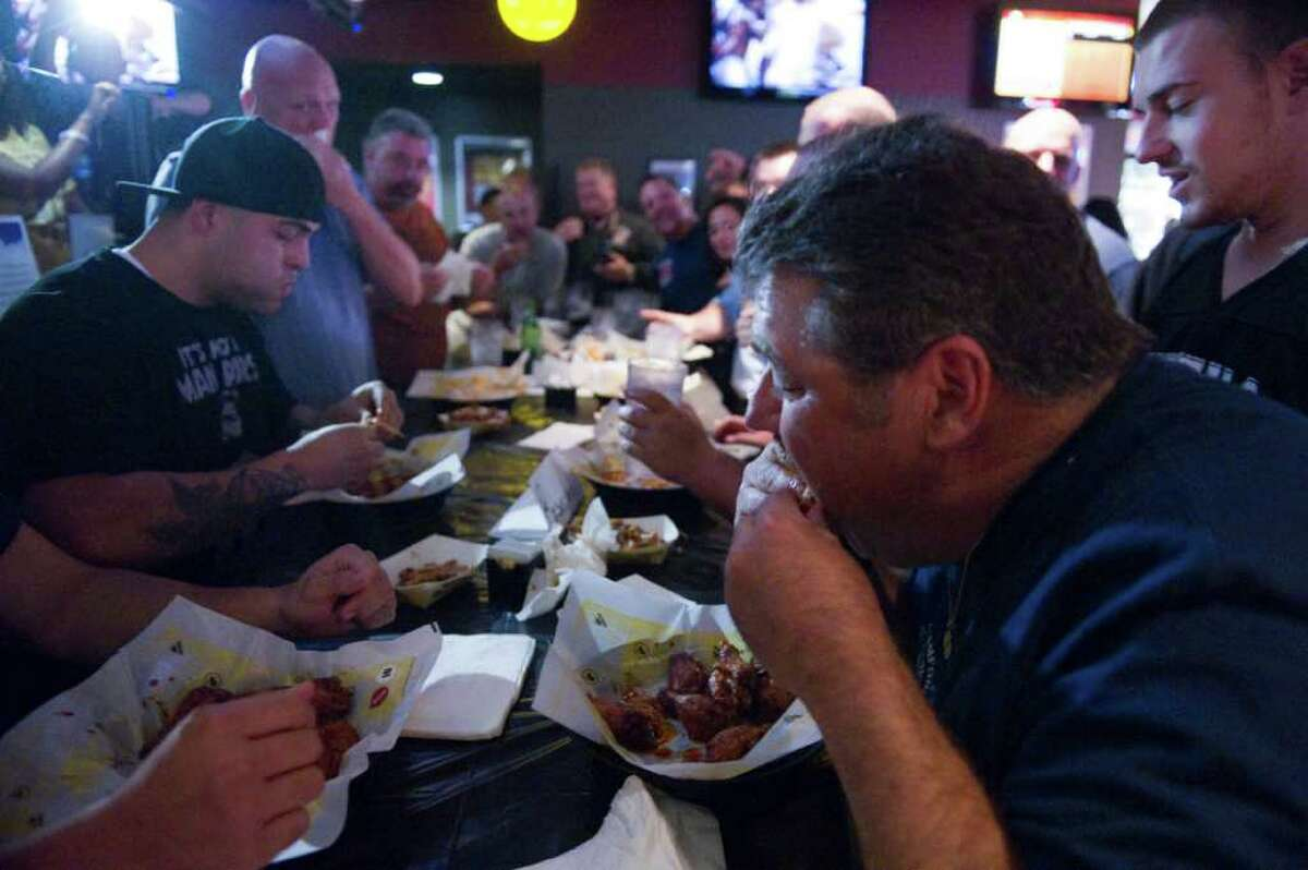 The 3rd Annual Stamford Guns 'N Hoses Wing Eating Challenge between Stamford Fire and Rescue and the Stamford Police Department at Buffalo Wild Wings in Stamford, Conn., October 19, 2011. The contest consists of 7 firefighters and 7 policemen dueling over individual plates of a dozen hot wings for the benefit of the American Lung Association.