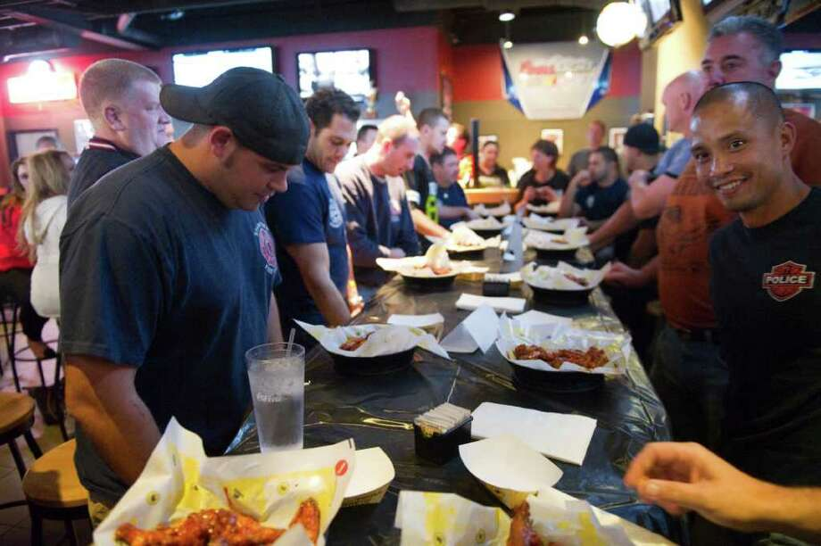 The 3rd Annual Stamford Guns 'N Hoses Wing Eating Challenge between Stamford Fire and Rescue and the Stamford Police Department at Buffalo Wild Wings in Stamford, Conn., October 19, 2011. The contest consists of 7 firefighters and 7 policemen dueling over individual plates of a dozen hot wings for the benefit of the American Lung Association. Photo: Keelin Daly / Stamford Advocate
