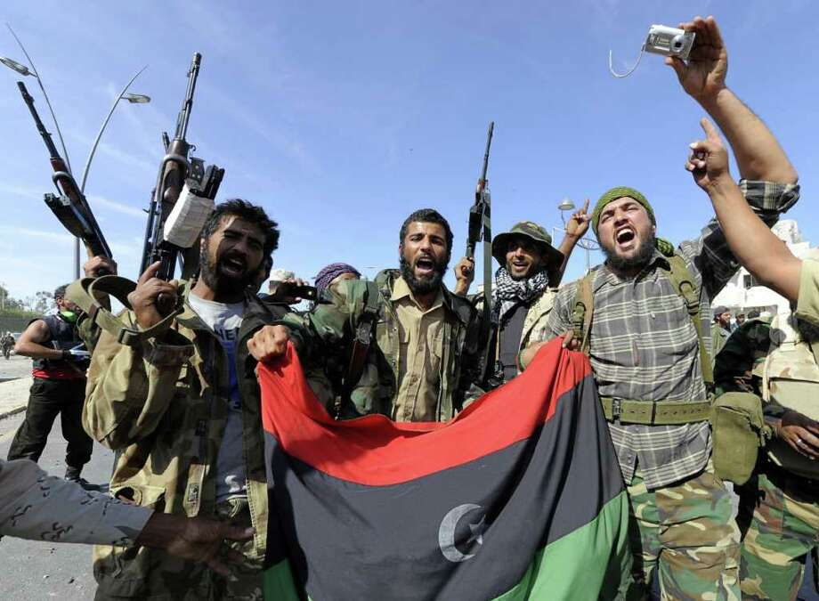 With camera in hand, a Libyan rebel (right) joins his comrades in celebrating the capture Col. Gadhafi's hometown. Photo: Philippe Desmazes/AFP/Getty Images / 2011 AFP