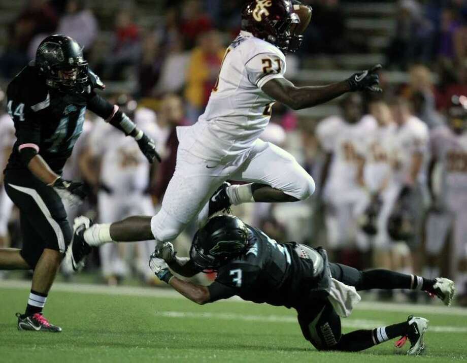 ERIC CHRISTIAN SMITH: FOR THE CHRONICLE ONE GIANT LEAP: Deer Park's Demetrius Banks (21), who amassed 193 yards and two TDs on 24 carries Thursday night, vaults Pasadena Memorial defender Reggie Turner. Photo: Eric Christian Smith