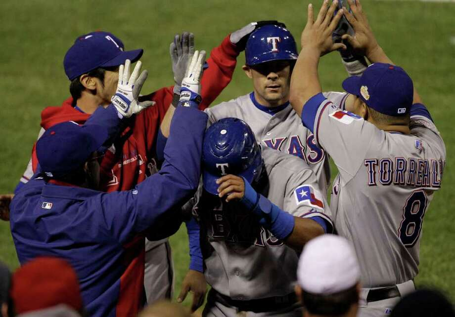 PAUL SANCYA : ASSOCIATED PRESS TEXAS TWO-STEP: Elvis Andrus, front, who scored the winning run, and Michael Young, rear, whose sacrifice fly drove him in, are congratulated in the Rangers' dugout during the ninth inning Thursday at Busch Stadium. Photo: Paul Sancya / AP