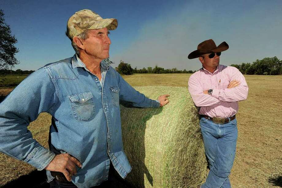 With a lack of rain in recent months, many local ranchers are resorting to purchasing hay from Louisiana and other states that experienced a wetter summer. Monroe Wilkins, left, is currently baling hay for Rancher Will McNeill who will feed his cattle with it this year.  Photo taken Wednesday, October 19, 2011 Guiseppe Barranco/The Enterprise