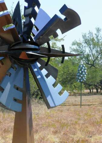 "Marshall Cunningham's steel sculpture ""Event Horizon"" was painted with a special chromium paint to change colors in the sunlight. Jerry Daniel's steel ""Bluebonnet"" is in the background. Photo: Photo By Steve Bennett"
