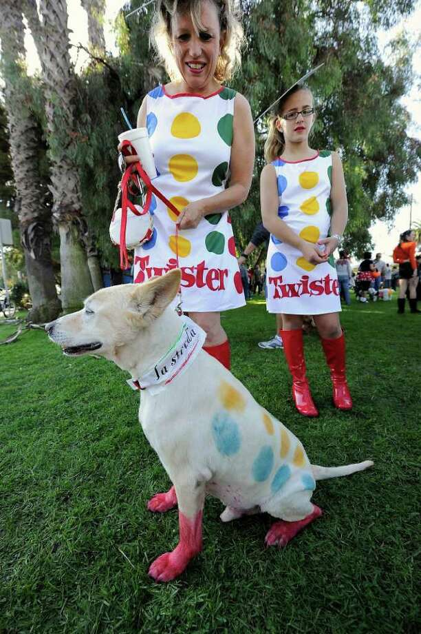 "Lisa Ramelow (L) and her niece Marissa Vigil and her dog Kyle are all dressed as the game ""Twister"" at the Halloween Dog Costume Parade in Long Beach, California on October 31, 2010.   AFP PHOTO / Robyn Beck Photo: ROBYN BECK, AFP/Getty Images / 2010 AFP"