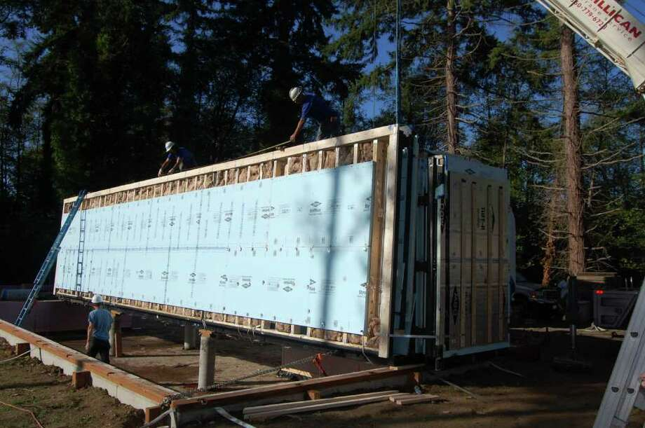 """Rather than have a home built on their Vashon Island property, Rich and Diana Mintz had one unfolded. Blu Homes builds the """"Glidehouse"""" in its Massachusetts factory using a steel frame with hinges, making it durable and allowing it to be folded down and shipped across the country to a home site, where the company completes the home in two weeks. It can be customized and feature floor-to-ceiling windows. The Mintz house has two bedrooms and two bathrooms, plus a 16-foot detached Glidehouse Pod with an extra bedroom and bath. It is the sixth Glidehouse built in Washington state, the second on Vashon Island and the first anywhere of an updated, larger version of the home. """"With its 60-foot 'wall of glass,' 14 foot-high ceilings, and abundant clerestory windows we knew this was a house that would allow us to take full advantage of the spectacular views from our lot,"""" Rich Mintz said in a news release, adding that he liked that the home was durable, precise and quick to build. See a video of the house being installed on the site. Photo: Blu Homes"""