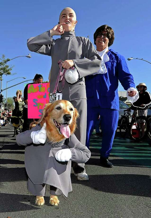 "A dog and his owners dress in ""Austin Powers"" costumes march in the Halloween Dog Costume Parade in Long Beach, California on October 31, 2010.   AFP PHOTO / Robyn Beck Photo: ROBYN BECK, AFP/Getty Images / 2010 AFP"