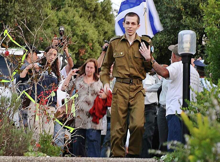 RETRANSMISSION TO PROVIDE ALTERNATIVE CROP OF JRL880 - In this photo released by the Israeli Defense Force, IDF, released Israeli soldier Gilad Schalit walks down the stairs into his home in Mitzpe Hila, northern Israel, after over five years in captivity, Tuesday, Oct. 18, 2011. Looking dazed, a thin and pale Gilad Schalit emerged from a pickup truck Tuesday under the escort of his Hamas captors and the Egyptian mediators who helped arrange the Israeli tank crewman's release after more than five years in captivity. (AP Photo/ IDF) EDITORIAL USE ONLY: / IDF