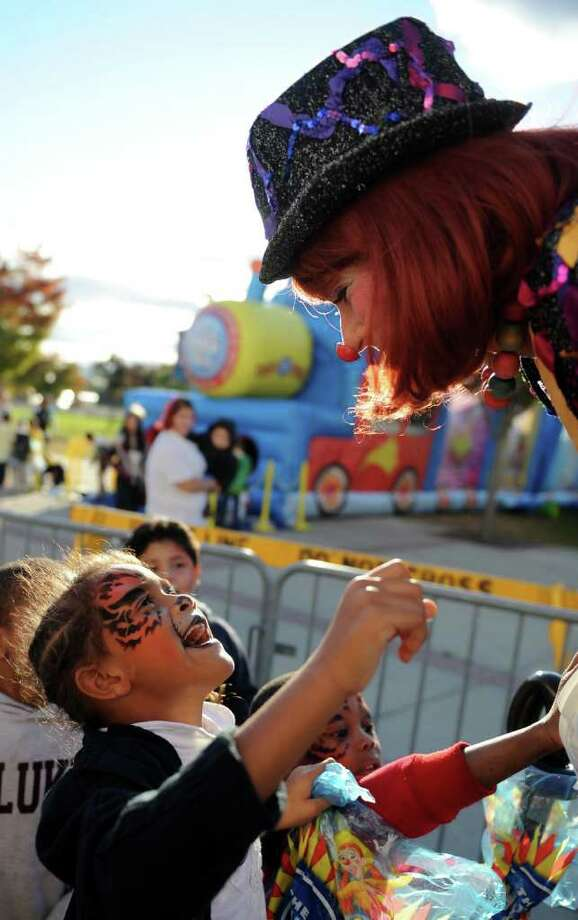Angelyna Upchurch, a second-grade student at Hall School, meets stilt walker, Gigi, during a block party with performers from the Ringling Bros. and Barnum and Baily Circus Friday, Oct. 21, 2011 outside the Webster Bank Arena at Harbor Yard in Bridgeport, Conn. Photo: Autumn Driscoll / Connecticut Post