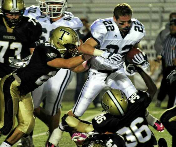 A helmetless Staples' #22 Joey Zelkowitz gets tackled Trumbull's #22 Billy O'Keefe, left, and #36 Sean Ramsay, during boys football action in Trumbull, Conn. on Friday October 21, 2011. Trumbull's #44 Don Cherry pulled off Zelkowitz's helmet and the team was penalized. Photo: Christian Abraham / Connecticut Post